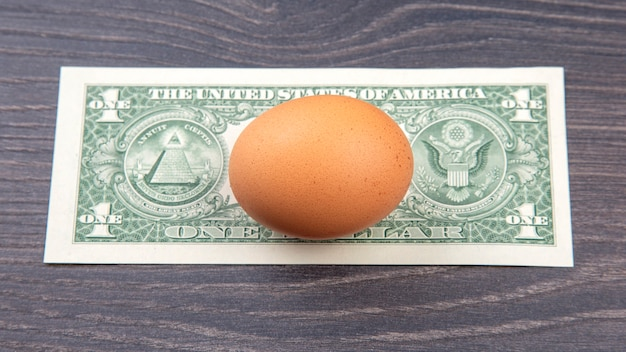 Uovo di gallina con il dollaro su un tavolo di legno. vendita e business di prodotti alimentari