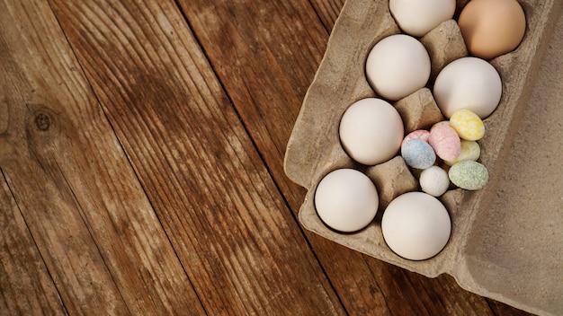 Uova di gallina in un vassoio di cartone e decorazioni pasquali su uno sfondo di legno