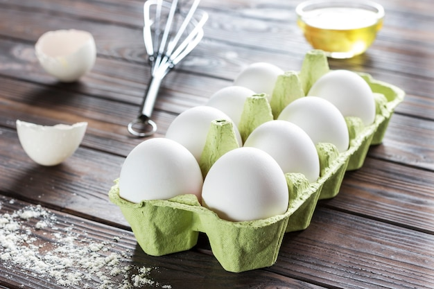 Uova di gallina in scatola di cartone, guscio d'uovo, uovo rotto nel piatto, frusta in metallo. avvicinamento