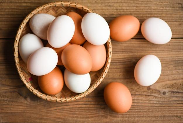 Le uova di gallina e le uova di anatra si raccolgono dai prodotti agricoli naturali in un cestino