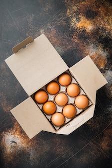 Uova di gallina in un set di vassoi per uova, su vecchio fondo rustico scuro, vista dall'alto piatta