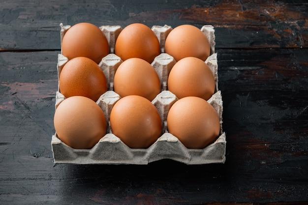 Uova di gallina in un vassoio della scatola delle uova insieme, sul vecchio fondo della tavola in legno scuro