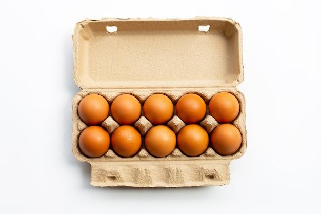 Uova di gallina in scatola per uova su sfondo bianco.