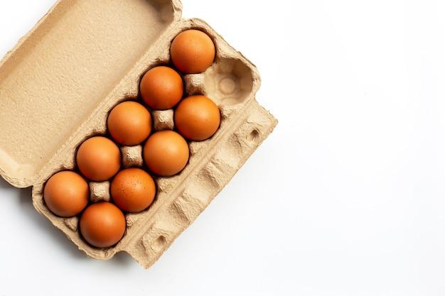 Uova di gallina in scatola per uova su una superficie bianca