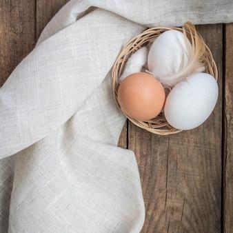 Uova di gallina e una piuma su un tavolo di legno