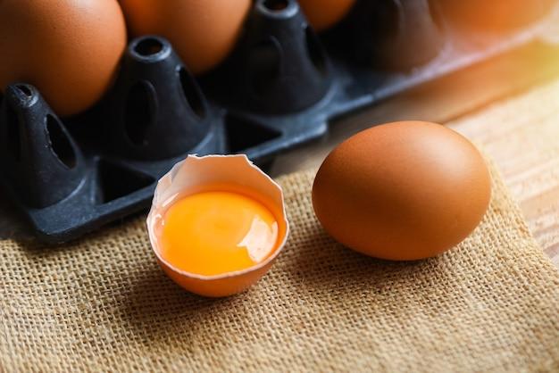 Uova di gallina da prodotti di fattoria naturali nella scatola concetto di mangiare sano / tuorlo d'uovo rotto fresco