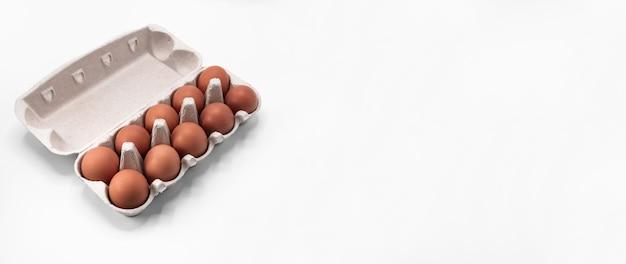 Uova di gallina in una scatola di uova aperta isolata