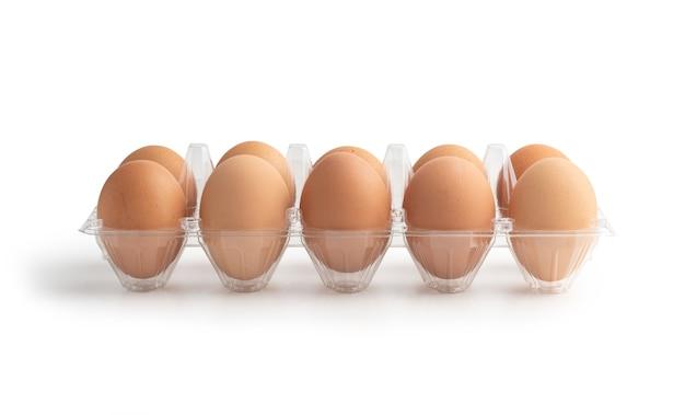 Uova di gallina nella scatola di plastica isolata sulla superficie bianca con tracciati di ritaglio