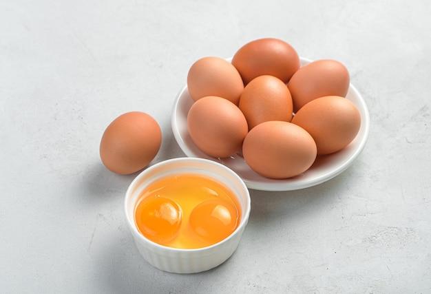 Uova di gallina in un piatto e tuorli d'uovo su uno sfondo chiaro. vista laterale, spazio per la copia. prodotti organici.
