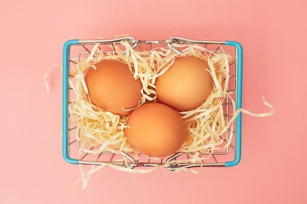 Uova di gallina in un carrello della spesa su uno sfondo rosa pastello, copia spazio, flatlay