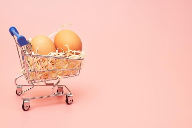 Uova di gallina in un carrello della spesa su uno sfondo rosa pastello, copia dello spazio