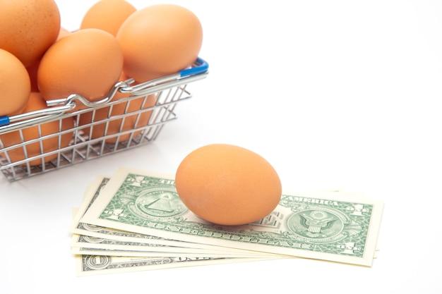 Uova di gallina in un cestino della drogheria del supermercato e dollari su una priorità bassa bianca. vendita e business di prodotti alimentari