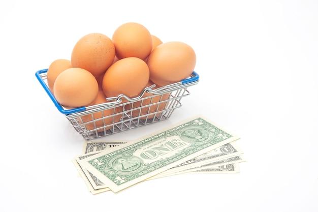 Uova di gallina in un cestino della drogheria del supermercato e dollari su una superficie bianca. vendita e business di prodotti alimentari
