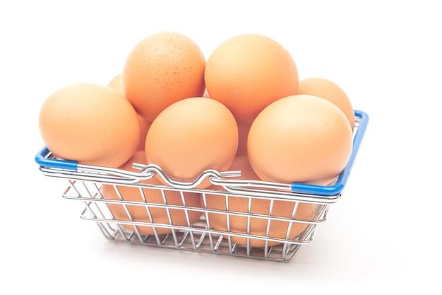 Uova di gallina in un cesto della spesa del supermercato su uno sfondo bianco.