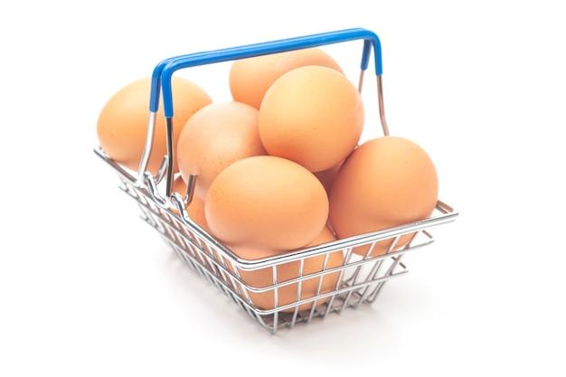 Uova di gallina in un cesto della spesa del supermercato su sfondo bianco.