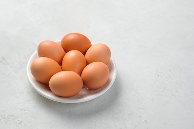 Uova di gallina su un piatto bianco su sfondo grigio
