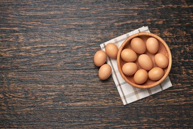 Uova di gallina in una ciotola di legno su un tavolo da cucina, vista dall'alto.