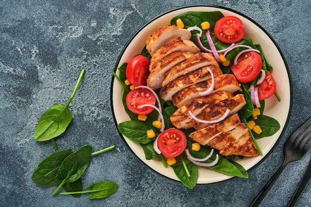 Filetto di pollo con insalata di spinaci, pomodorini, fiordaliso e cipolla. cibo salutare. dieta cheto, concetto di pranzo dietetico. vista dall'alto su sfondo bianco.