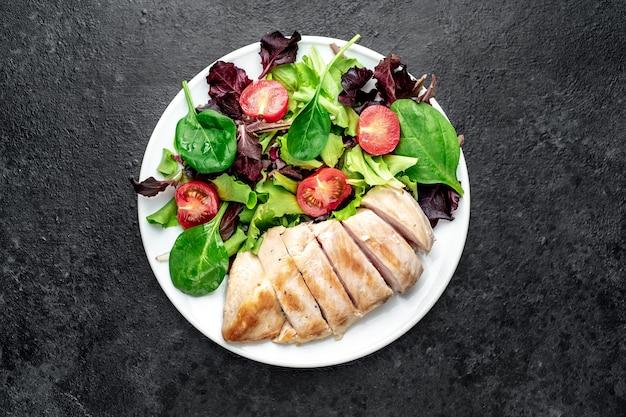 Filetto di pollo con insalata e spinaci cibo sano sul tavolo di pietra