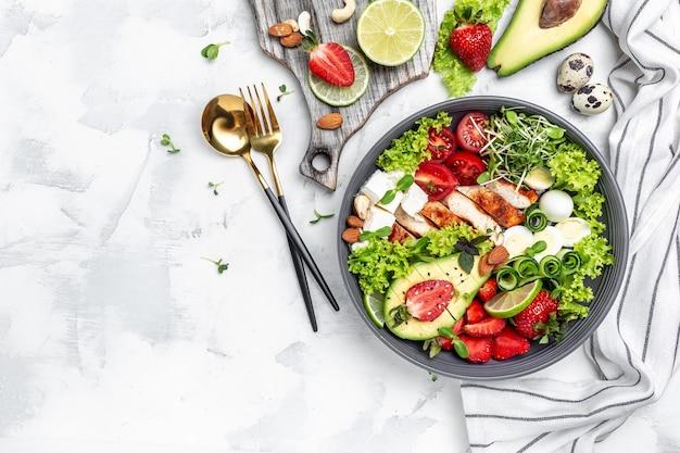 Filetto di pollo con insalata con avocado, formaggio feta, uova di quaglia, fragole, noci e lattuga su sfondo bianco. cibo sano, dieta keto, concetto di pranzo dietetico. vista dall'alto.