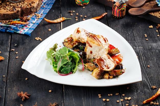 Filetto di pollo con salsa e verdure sulla tavola di legno nera