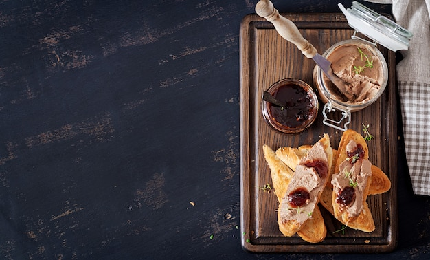 Paté di fegato fatto in casa di pollo in barattolo di vetro con toast e marmellata di mirtilli rossi con peperoncino.