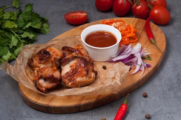 Spiedini di pollo con salsa di pomodoro su tavola di legno