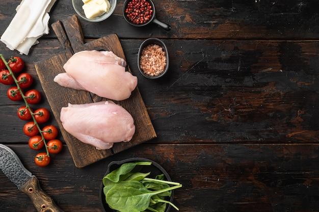 Ingredienti di pollo kiev con filo, filetto, erbe e set di burro, su un vecchio tavolo di legno scuro