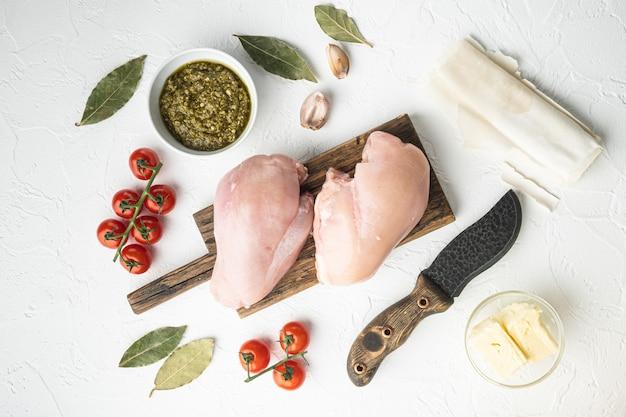 Ingredienti di pollo kiev con set filo, su tavolo in pietra bianca, vista dall'alto piatta