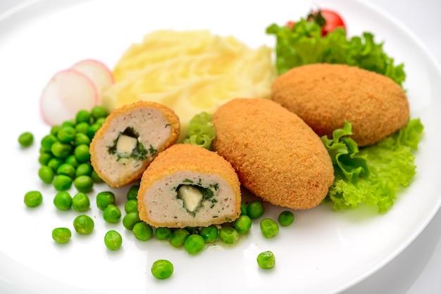 Pollo alla kiev, cucina ucraina. cotolette di pollo in pangrattato farcite con burro ed erbe aromatiche, servite con purè di patate e piselli, su una piastra bianca