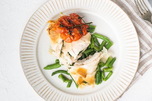 Pollo alla kiev con set di aglio orsino, con pomodorini al forno e fagiolini, su pietra bianca