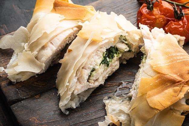 Pollo alla kiev con set di aglio selvatico, con pomodorini al forno, su tavola da portata, su vecchio tavolo di legno scuro