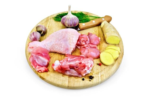 Coscia di pollo tagliata su una tavola rotonda con aglio, prezzemolo, zenzero e un coltello isolato su sfondo bianco