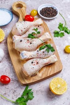 Cosce di pollo con spezie e sale pronti per la cottura sul tagliere.