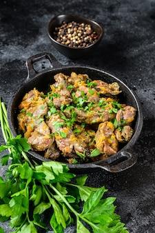 Fegato di pollo, cuore e stomaco in salsa di panna. sfondo nero. vista dall'alto.