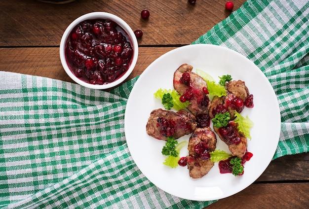 Fegatini di pollo con salsa di mirtilli rossi e lattuga. vista dall'alto