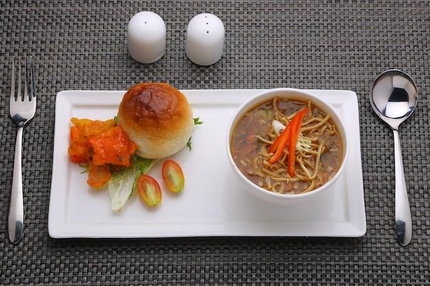 Zuppa di pollo manchow guarnita con verdure disposte in una ciotola bianca con sfondo bianco