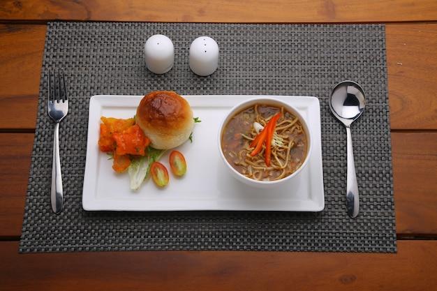 Zuppa di pollo manchow guarnita con verdure disposte in una ciotola bianca