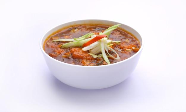 Zuppa di pollo alla manciuria guarnita con verdure disposte in una ciotola bianca