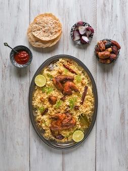 Pollo mandi con le date su una tavola di legno. cucina araba