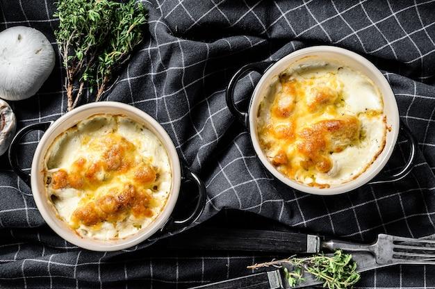 Casseruola di pollo e funghi con formaggio in una pentola di terracotta
