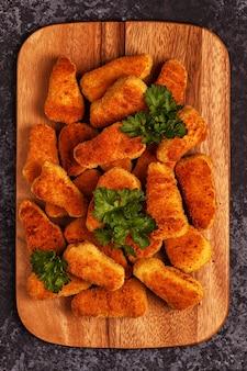 Bocconcini di pollo con salse su fondo scuro