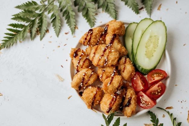 Le crocchette di pollo vengono servite con cetriolo fresco e pomodori