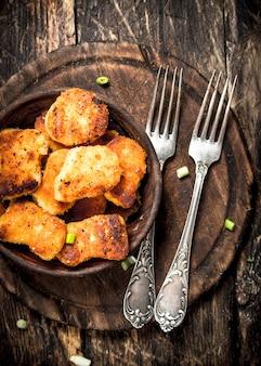 Pepite di pollo in una ciotola con le forchette. su uno sfondo di legno.
