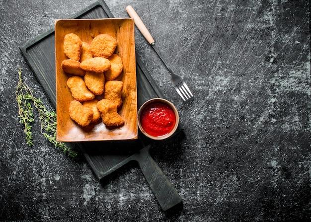 Pepite di pollo sul tagliere con timo e salsa di pomodoro sul tavolo rustico