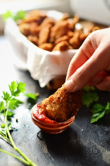 Bocconcini di pollo su una superficie scura. pesce e carne alla griglia in pastella. bastoncini di pesce. bastoncini di carne. pepite con pomodoro e prezzemolo in un cestino. posto per il tuo testo.