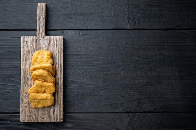 Pepite di pollo fritte sulla tavola di legno nera
