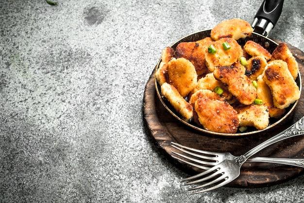 Bocconcini di pollo in padella. su fondo rustico.