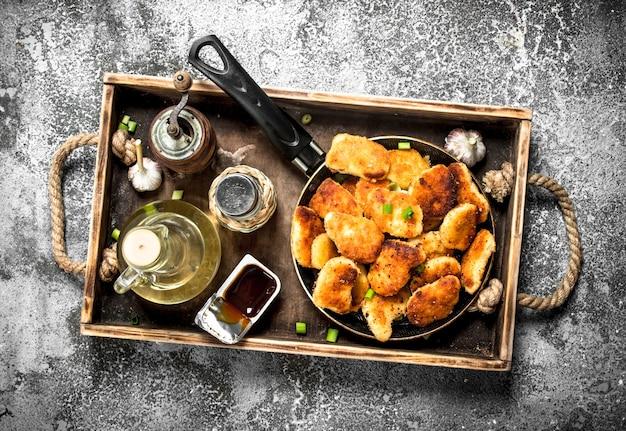 Bocconcini di pollo in padella con spezie e salsa.