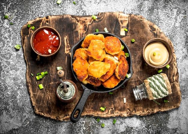 Bocconcini di pollo in padella con salse diverse. su fondo rustico.